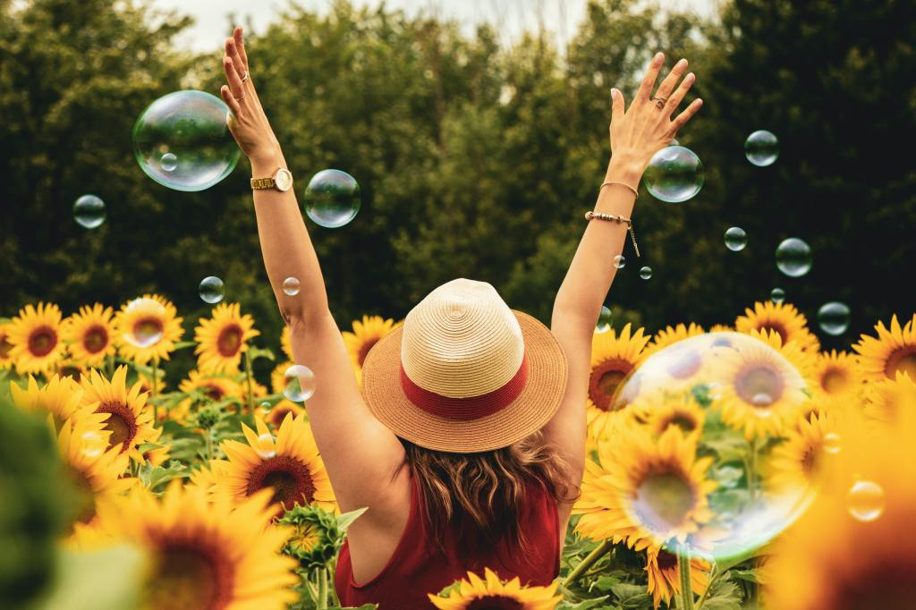 woman wearing a hat in sunflower field with her arms up