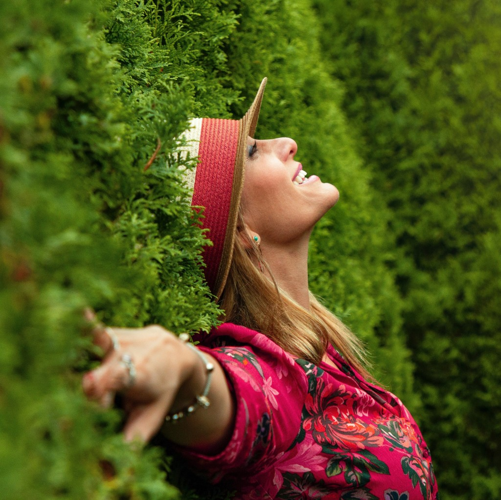 woman with blond hair wearing a red and beige hat stretching her arms out to the side in front of green bushes