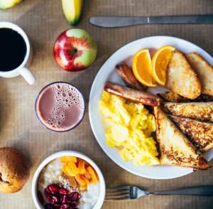 full American breakfast, eggs, sausage, toast, coffee, juice, and fruit