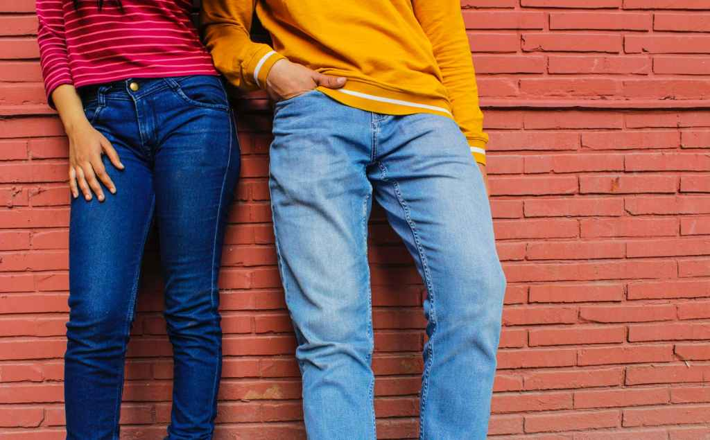 Woman and man standing against an orange brick wall. They are wearing jeans blue jeans and a red and orange shirt.